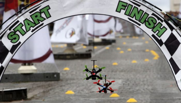 Drones cross the start and finish line during a race in Paris, Sunday, Sept. 4, 2016. The city is hosting its first Drone Festival on Sunday, including a race along the Champs-Elysees. Drones of varying shapes and sizes are zipping along the avenue, lined with trees and luxury stores, in a circuit that stops just shy of the Arc de Triomphe. (AP Photo/Christophe Ena)